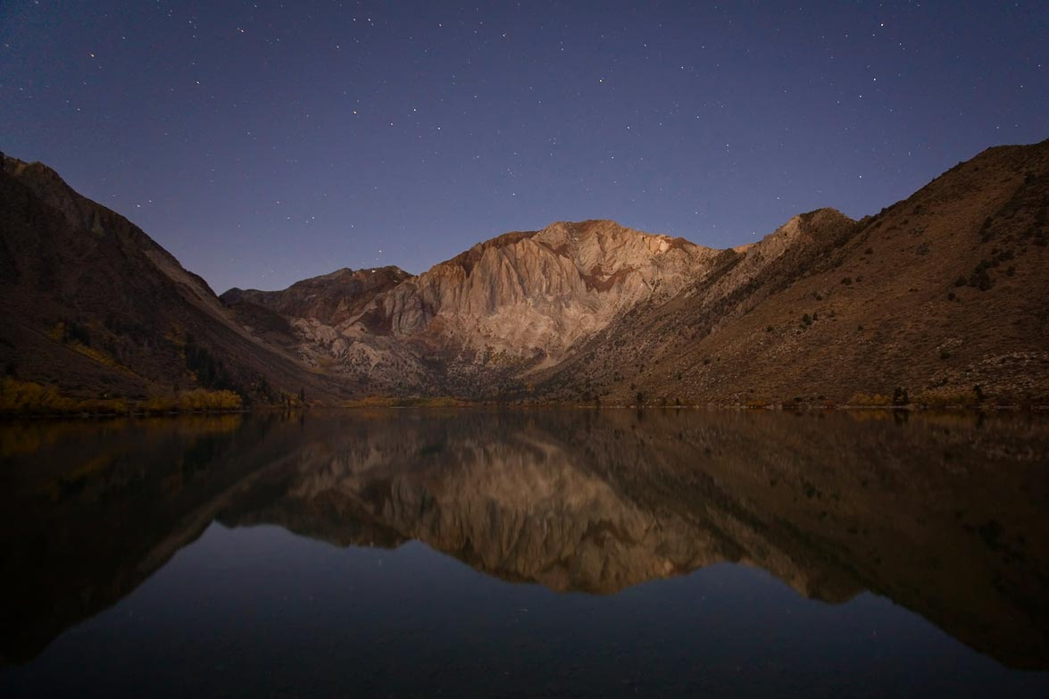 A night time view of Convict Lake with stars overhead